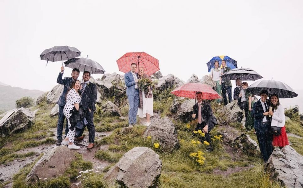 Happy bride, groom and guests shelter under umbrellas, standing on a rocky hill at an outdoor wedding