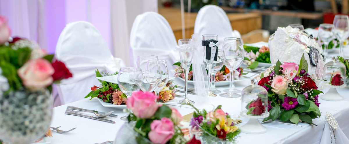 The top table at a wedding, decorated with flowers, glassware and linen